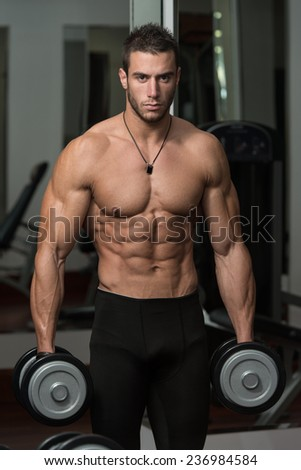 Fit Athlete Working Out Biceps - Dumbbell Concentration Curls - stock photo