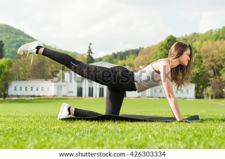 Fit attractive woman doing aerobic exercise in the park as healthy lifestyle concept - stock photo