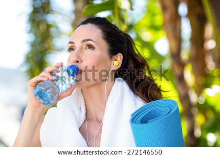 Fit beautiful brunette drinking water while listening music on a sunny day - stock photo