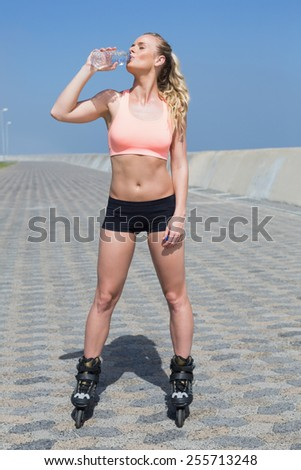Fit blonde drinking water in roller blades on a sunny day - stock photo