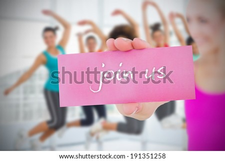 Fit blonde holding card saying join us against fitness class in gym - stock photo
