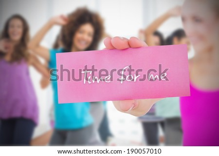 Fit blonde holding card saying time for me against dance class in gym - stock photo