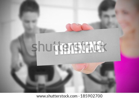 Fit blonde holding card saying training against bike class in gym
