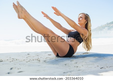 Fit blonde in core balance pilates pose on the beach on a sunny day - stock photo