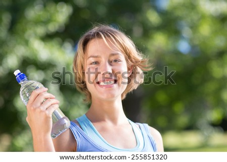 Fit blonde in the park with water bottle on a sunny day - stock photo