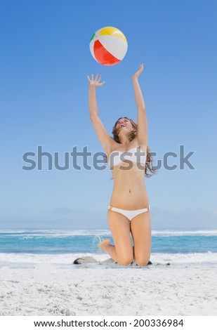 Fit blonde in white bikini throwing beach ball on a sunny day