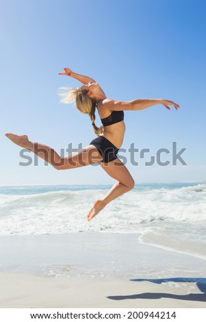 Fit blonde jumping gracefully on the beach on a sunny day - stock photo