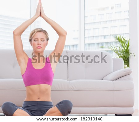 Fit blonde meditating in lotus pose with arms raised at home in the living room - stock photo