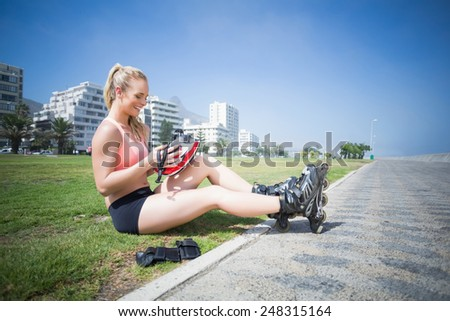 Fit blonde putting on her roller blades on a sunny day - stock photo