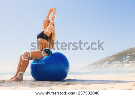 Fit blonde sitting on exercise ball at the beach against fitness interface - stock photo