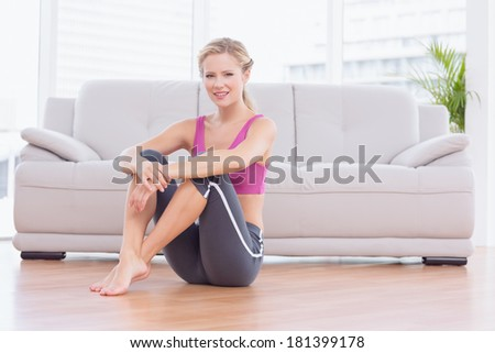 Fit blonde sitting on floor smiling at camera at home in the living room