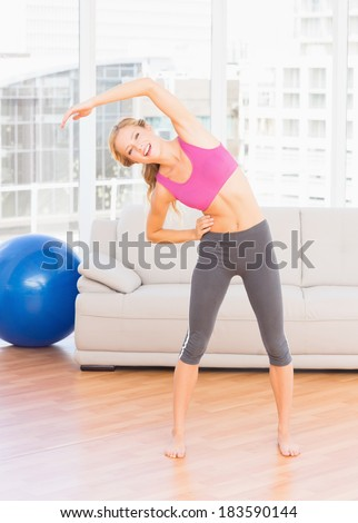 Fit blonde smiling at camera while stretching at home in the living room - stock photo