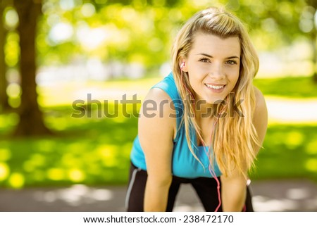 Fit blonde smiling in the park on a sunny day