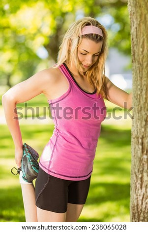 Fit blonde stretching against a tree on a sunny day - stock photo