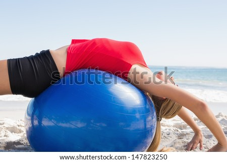 Fit blonde stretching back on exercise ball on the beach - stock photo
