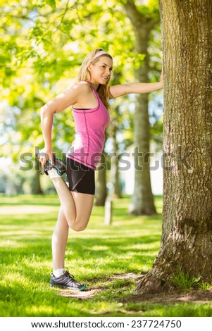 Fit blonde stretching her leg on a sunny day