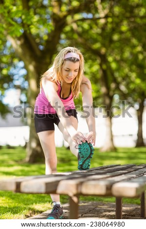 Fit blonde stretching her leg on a sunny day - stock photo