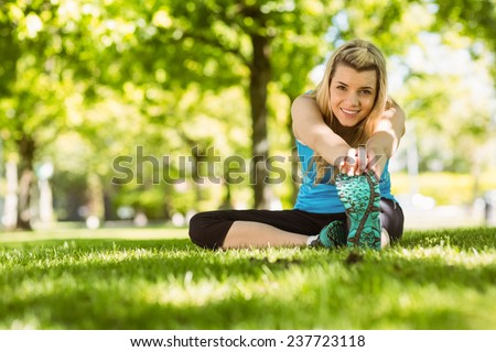 Fit blonde stretching on the grass on a sunny day - stock photo