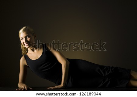 Fit blonde woman stretching and exercising on black background