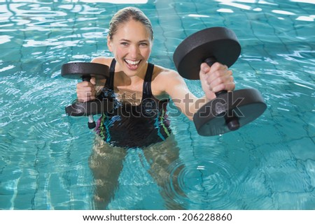 Fit blonde working out with foam dumbbells in swimming pool at the leisure centre - stock photo