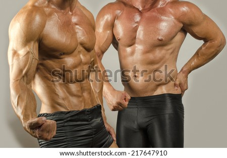Fit body versus fat body, flexing muscles. Two men showing their biceps,abs, chest and shoulders in a contest - stock photo