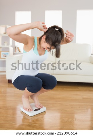 Fit brunette cheering on the weighing scales viargeat home in the living room - stock photo