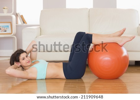 Fit brunette doing sit ups with exercise ball at home in the living room - stock photo
