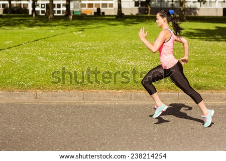 Fit brunette going faster on path in the park on a sunny day - stock photo