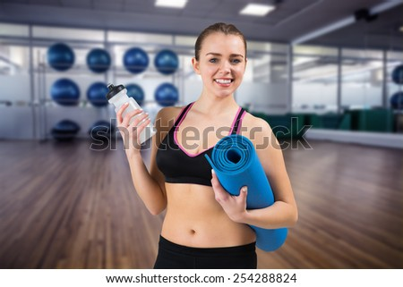 Fit brunette holding mat and sports bottle against large empty fitness studio with shelf of exercise balls - stock photo