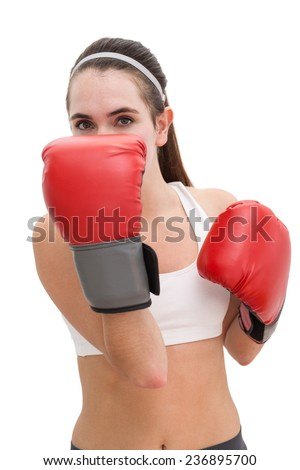 Fit brunette in boxing gloves on white background