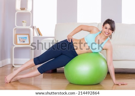 Fit brunette in plank position on exercise ball at home in the living room - stock photo