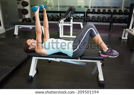 Fit brunette lifting dumbbells on bench at the gym - stock photo