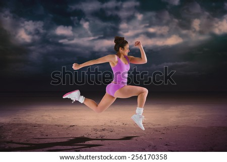 Fit brunette running and jumping against dark cloudy sky