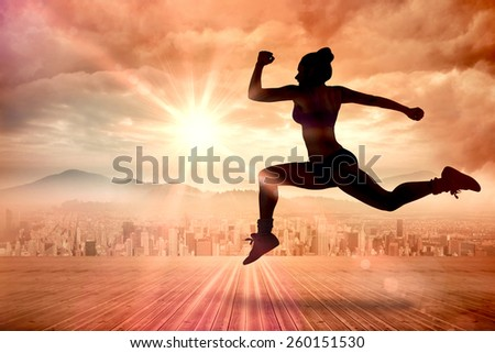 Fit brunette running and jumping against sun shining over city - stock photo