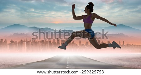 Fit brunette running and jumping against sun shining over road and city
