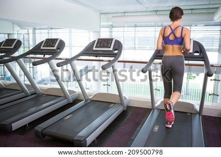 Fit brunette running on the treadmill at the gym - stock photo