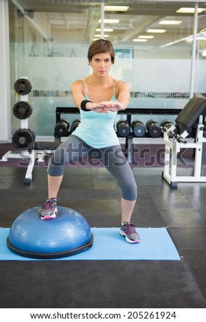 Fit brunette using bosu ball for squats at the gym - stock photo