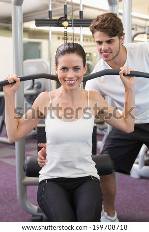 Fit brunette using weights machine for arms with trainer helping at the gym