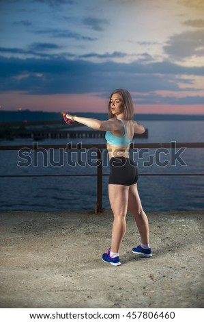Fit caucasian woman doing exercise with dumbbells on sea pier at sunset. Fitness workout outdoors - stock photo