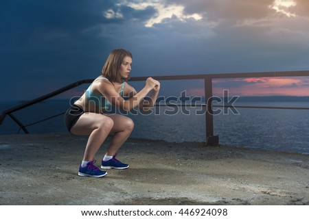 Fit caucasian woman in sportswear doing squats on sea pier at sunset. Fitness workout outdoors - stock photo