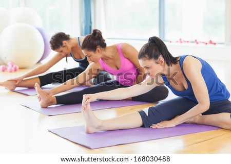 Fit class stretching legs on mats at yoga class in fitness studio - stock photo