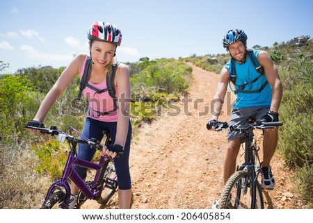 Fit couple cycling down mountain trail smiling at camera on a sunny day