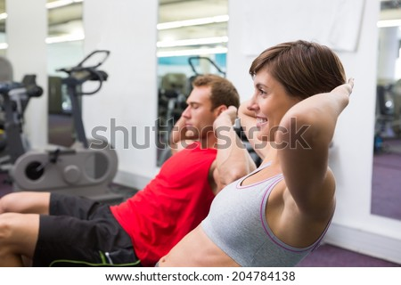 Fit couple doing sit ups on exercise ball at the gym