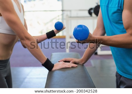 Fit couple exercising with blue dumbbells at the gym - stock photo