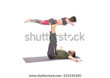 Fit couple in a yoga pose on a grey mat - isolated on white