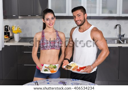 fit couple in the kitchen, holding plates of healthy food: rice, chicken grill, broccoli, carrots, mushrooms, potatoes, salmon, tomato, red peppers - stock photo
