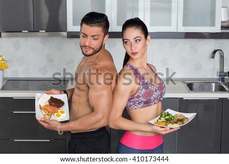 fit couple looking angry in the kitchen; animal versus plant proteins: one plate with beef, eggs, salmon, cheese and chicken grill and another with nuts, mushrooms, broccoli, lentil, hummus and quinoa
