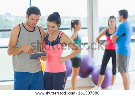 Fit couple looking at digital table with friends chatting in background in bright exercise room - stock photo