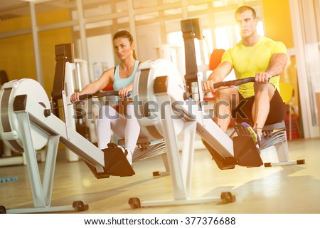 Fit  couple on row machine in gym, sport, fitness, lifestyle, and people concept - stock photo