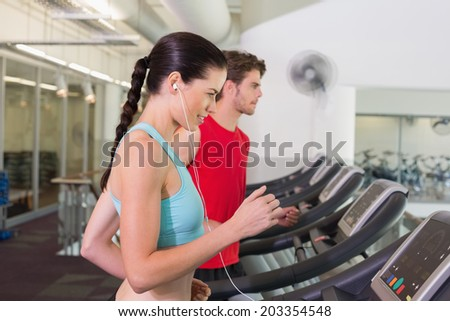 Fit couple running together on treadmills at the gym - stock photo